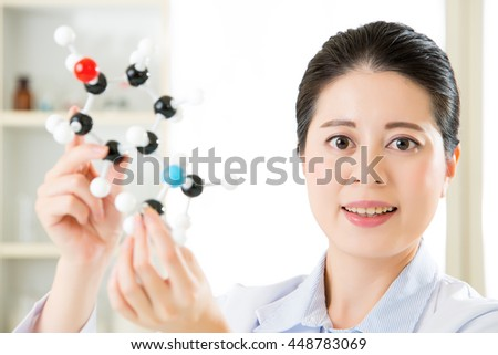 asian female scientist Examining the building blocks of life with molecular model in laboratory - stock photo