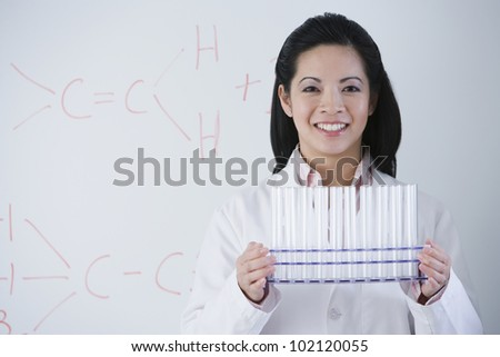 Asian female scientist holding rack of vials - stock photo