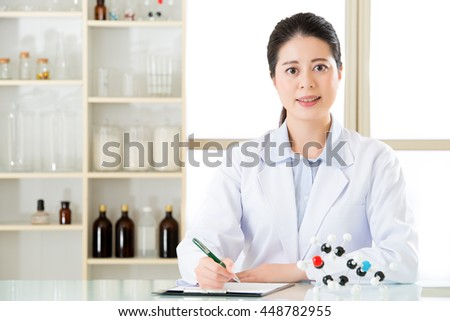 asian female scientist recording Chemical formula on clipboard for science research - stock photo