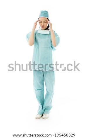 Asian female surgeon suffering from headache - stock photo
