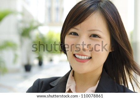 Asian female with her cheerful smile, outside modern building. - stock photo