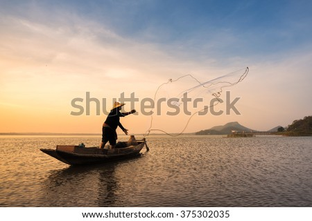 Asian fisherman on wooden boat casting a net for catching freshwater fish in nature river in the early morning before sunrise - stock photo