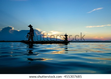 asian fisherman silhouette fishing on the both during sunset. - stock photo