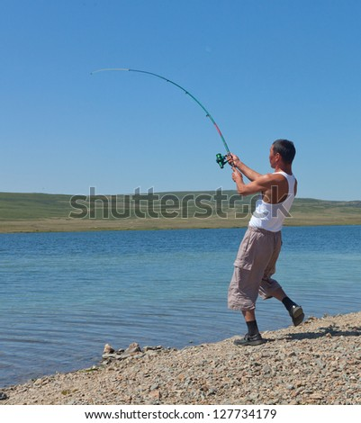 Asian fisherman throws spinning in a mountain lake