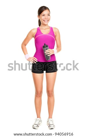 Asian fitness woman model standing in sporty gym clothing smiling happy holding water bottle. Fit young multiracial Asian Caucasian female fitness model isolated in full length on white background.