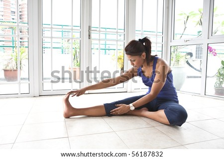 Asian fitness woman stretching her hamstring while being on the floor - stock photo