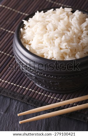 Asian food: boiled rice in a black bowl close-up and chopsticks. vertical  - stock photo