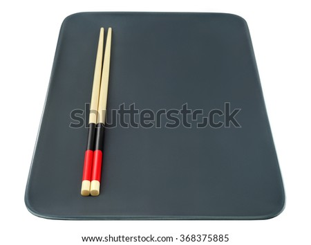 Asian food concept with plate and chopsticks. Black square empty dish with chinese sticks isolated on white. - stock photo