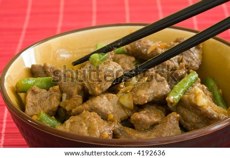 asian food of beef and vegetables on brown bowl and black chopstick - stock photo