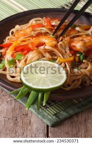 Asian food: rice noodles with shrimp and vegetables close-up on a plate. vertical  - stock photo