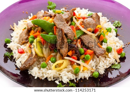 Asian food - roast meat with vegetables and rice - stock photo