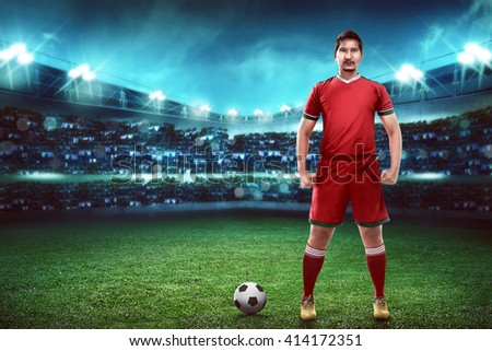 Asian football player standing on green grass stadium
