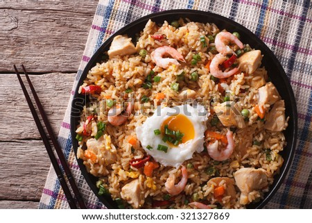 Asian fried rice nasi goreng with chicken, prawns, egg and vegetables close-up horizontal view from above - stock photo
