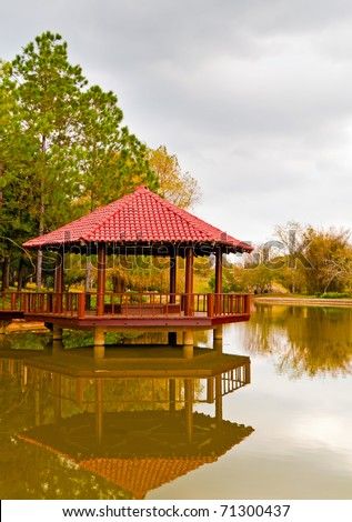 Asian garden featuring a wooden pavilion with reflections on a lake
