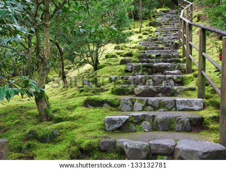 Asian Garden Stone staircase with wood railing and surrounding green grass and trees - stock photo