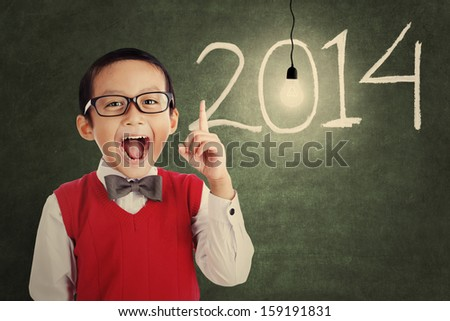 Asian genius student with light bulb and number of new year 2014 shot in a classroom - stock photo