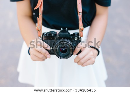 Asian girl and black vintage film camera - stock photo