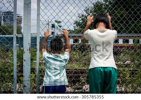 asian girl and boy sad  hand hold jail at Railroad,railway station - stock photo