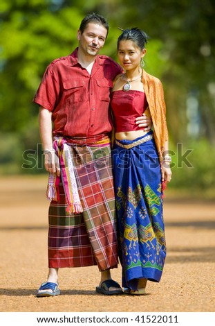 asian girl and caucasian man wearing traditional thai clothes - stock photo