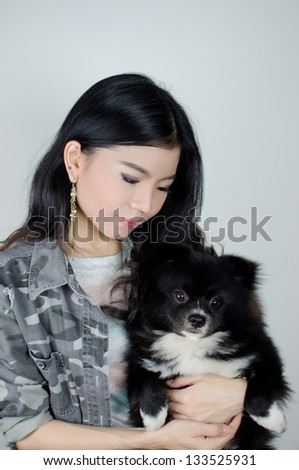 Asian girl carrying cute black pommeranian puppy - stock photo