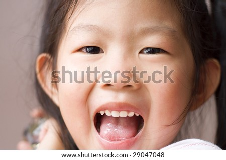 Asian girl. Close-up shot of a young Asian girl with smile on her face. - stock photo