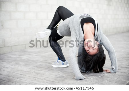 Asian girl doing bridge pose in gym clothes. - stock photo