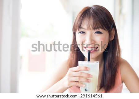 Asian girl drinking a glass of beverage with straw in cafe. Young woman living lifestyle. - stock photo