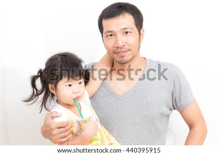Asian girl drinking juice and hugging her father over white background - stock photo