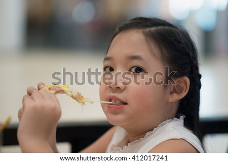 Asian girl eating a piece of pizza in a restaurant - stock photo