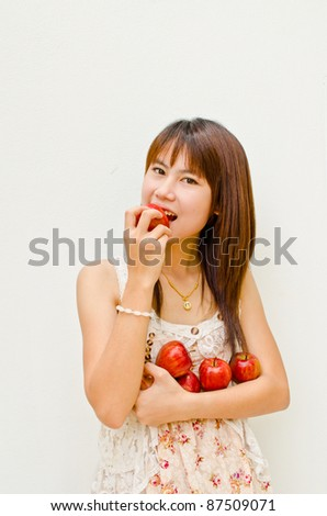 Asian girl eating apple on white background