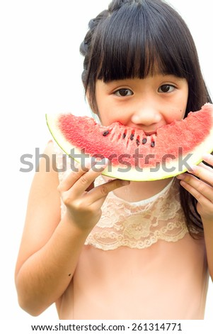 Asian girl eating slice of watermelon isolated on white background.