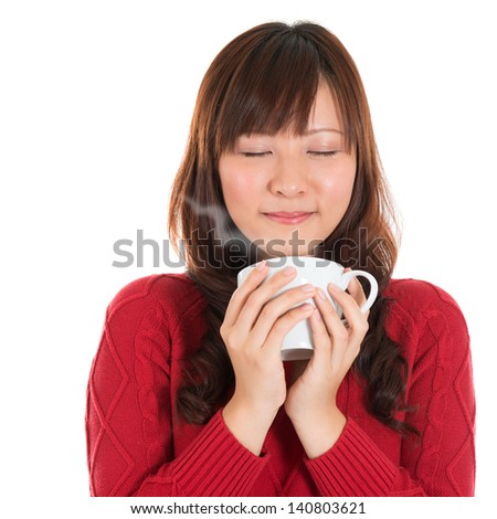 Asian girl enjoying a cup of coffee, with coffee smoke, isolated on white background. Beautiful mixed Asian model. - stock photo