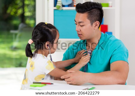 Asian girl examining her dad with stethoscope - stock photo