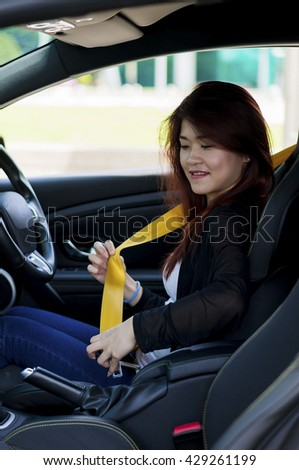 Asian Girl fastening the seat belt.  - stock photo