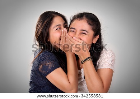 Asian girl friends gossiping. A girl giggling when her friend whispering something funny - stock photo