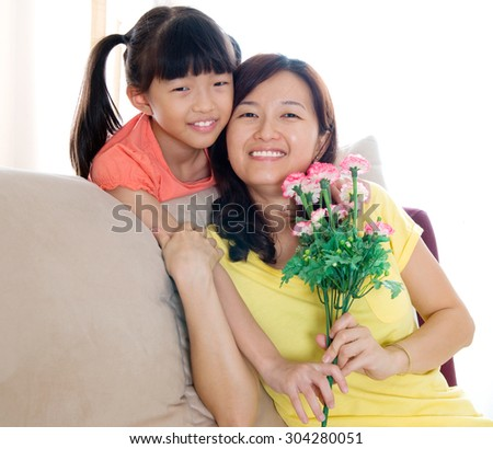 Asian girl giving carnation flower to mother on mothers day - stock photo