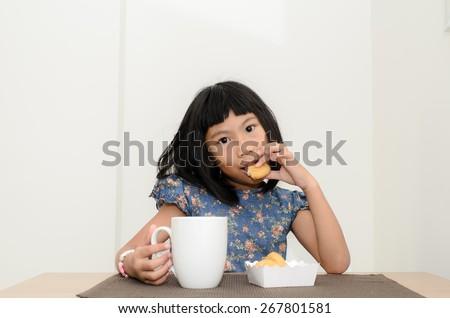 Asian girl having breakfast at home. - stock photo