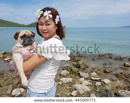 Asian girl holding a small cute puppy pug dog in her arms on the beach - stock photo