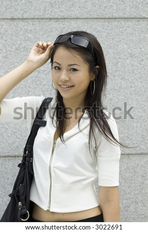 Asian girl holding pair of sunglasses - stock photo
