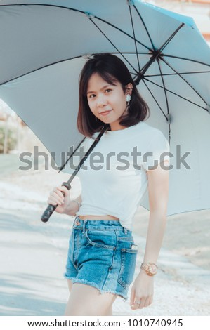 Asian girl holds an umbrella and looks at something.Asian girl with a beautiful white shirt standing poses with an umbrella and smiling.
