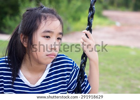 Asian girl in a bored mood at playground. - stock photo