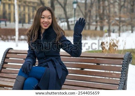 Asian girl in blue coat on the bench raised in greeting hand - stock photo