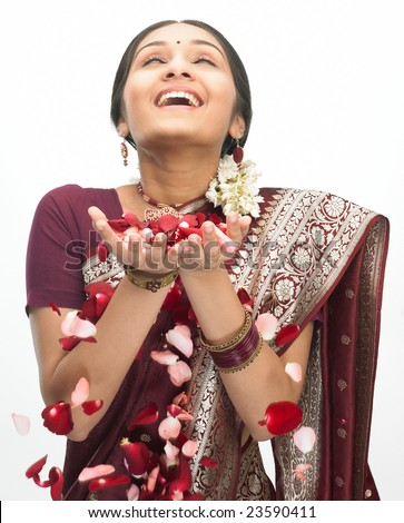 Asian girl in silk sari playing with the rose petals - stock photo