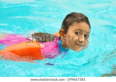 Asian girl in swimmer class with float bands. Indian child learning swimming in pool. - stock photo
