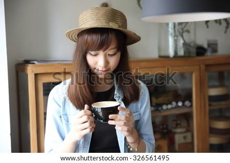 Asian girl indoor drinking coffee - stock photo