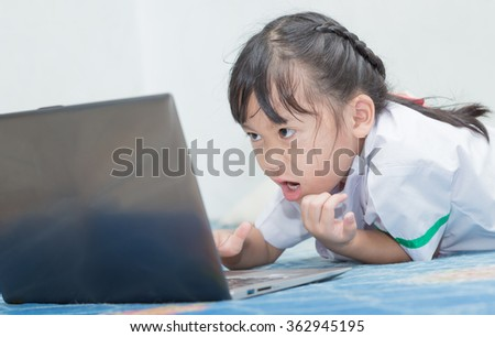 Asian Girl. Intensely Playing or Working on a Laptop Computer.