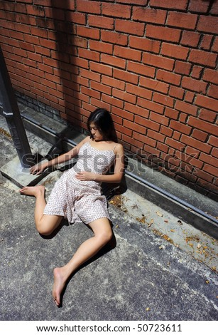 Asian girl is passed out in the gutter - stock photo