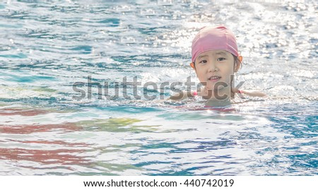 Asian girl is playing in the pool