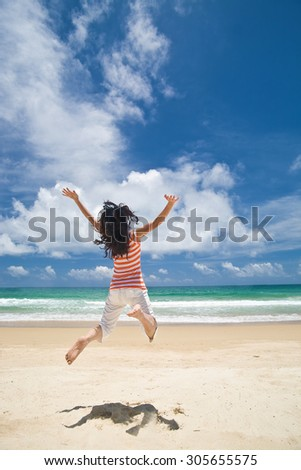 Asian girl jumping on beach on a sunny day - stock photo