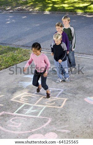 Asian girl jumping on hopscotch board with friends watching.  Ages 7 to 9 - stock photo
